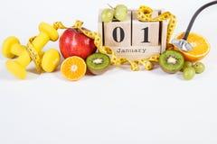 Cubez le calendrier, les fruits, les haltères et le ruban métrique, nouvelles années de résolutions Photo stock