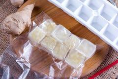 Cubi congelati dello zenzero in insetto su un tagliere su una tavola di legno Fotografia Stock