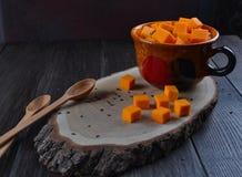 Cubi crudi del taglio della zucca in una tazza Fotografia Stock Libera da Diritti