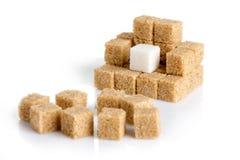 Cubi della canna da zucchero marroni e del bianco raffinato Immagine Stock
