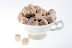 Cubi della canna da zucchero in tazza del porcelalain isolata su fondo bianco Fotografia Stock
