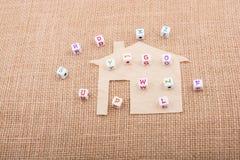 Cubi della lettera sulla casa tagliata di carta Fotografie Stock