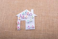 Cubi della lettera sulla casa tagliata di carta Immagini Stock Libere da Diritti
