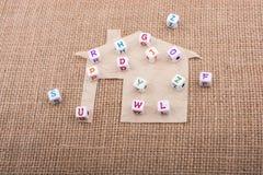 Cubi della lettera sulla casa tagliata di carta Immagini Stock