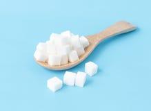 Cubi dello zucchero del primo piano sul fondo blu bianco del cucchiaio di legno Fotografia Stock