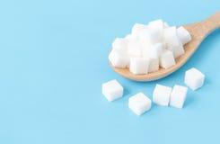 Cubi dello zucchero del primo piano sul fondo blu bianco del cucchiaio di legno Immagine Stock