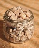 Cubi dello zucchero di canna di Brown nel barattolo di vetro Immagini Stock