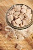Cubi dello zucchero di canna di Brown nel barattolo di vetro Fotografia Stock