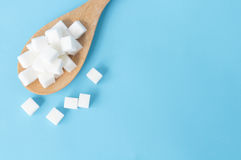 Cubi dello zucchero di vista superiore del primo piano sul backgrou blu bianco del cucchiaio di legno Fotografia Stock Libera da Diritti