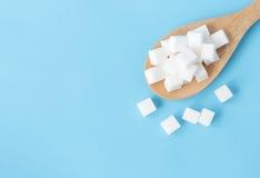Cubi dello zucchero di vista superiore del primo piano sul backgrou blu bianco del cucchiaio di legno Fotografie Stock