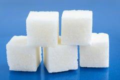 Cubi dello zucchero sul blu Immagini Stock
