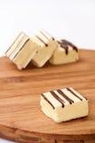 Cubi di cioccolata bianca su un bordo di legno della cucina Fotografie Stock