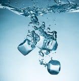 Cubi di ghiaccio che spruzzano nell'acqua fotografia stock