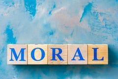 Cubi di legno con la parola MORALE sulla tavola blu immagine stock libera da diritti