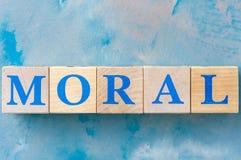 Cubi di legno con la parola MORALE sulla tavola blu fotografie stock libere da diritti