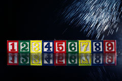 Cubi di legno e numeri isolati su fondo nero Fotografie Stock