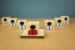 cubi di legno sotto forma di capi e di subalterni, subordinazione del personale su un fondo blu immagini stock libere da diritti