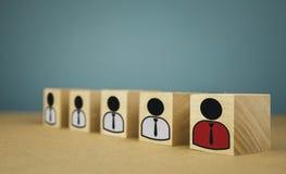 cubi di legno sotto forma di capi e di subalterni, subordinazione del personale su un fondo blu fotografia stock