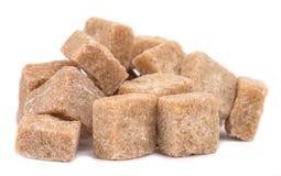 Cubi di marrone della canna da zucchero isolati su bianco Immagini Stock