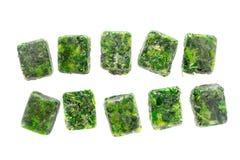 Cubi di spinaci congelati sui precedenti bianchi Fotografia Stock