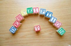 Cubi educativi del giocattolo con le lettere organizzate per visualizzare parola DESCRIZIONE - pubblicare i meta dati e motore di immagini stock