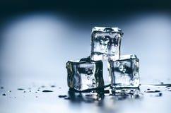 Cubi ghiacciati che si fondono su una tavola blu con la riflessione Acqua Fusione del ghiaccio Immagini Stock