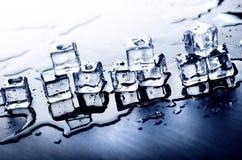 Cubi ghiacciati che si fondono su una tavola blu con la riflessione Acqua Fusione del ghiaccio Fotografie Stock