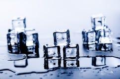 Cubi ghiacciati che si fondono su una tavola blu con la riflessione Acqua Fusione del ghiaccio Immagini Stock Libere da Diritti