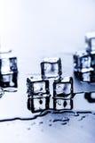 Cubi ghiacciati che si fondono su una tavola blu con la riflessione Acqua Fusione del ghiaccio Immagine Stock