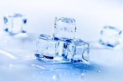 Cubi ghiacciati che si fondono su una tavola blu con la riflessione Acqua Fusione del ghiaccio Fotografia Stock
