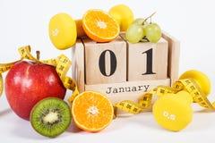 Cubi il calendario, i frutti, le teste di legno e la misura di nastro, nuovi anni di risoluzioni Fotografia Stock Libera da Diritti