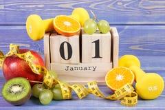 Cubi il calendario, i frutti, le teste di legno e la misura di nastro, nuovi anni di risoluzioni Fotografie Stock Libere da Diritti