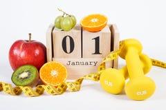 Cubi il calendario, i frutti, le teste di legno e la misura di nastro, nuovi anni di risoluzioni Fotografie Stock
