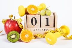 Cubi il calendario, i frutti, le teste di legno e la misura di nastro, nuovi anni di risoluzioni Fotografia Stock