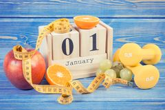 Cubi il calendario, i frutti, le teste di legno e la misura di nastro, nuovi anni di concetto di risoluzioni Immagini Stock