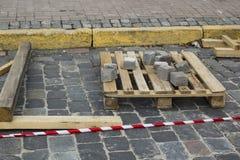 Cubi posti del granito su un pallet alla strada di pietra Ricostruzione del marciapiede con ciottolo fotografie stock