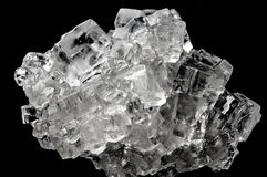 Cubic salt crystal aggregate against black background royalty free stock image
