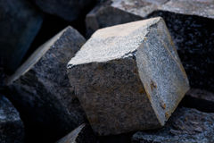 Cubic shape stone blocks. A pile of hard stone blocks of cubic form or shape and gray color. The construction or building blocks of granite are to be used for Stock Photos