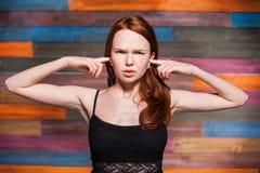 Cubierta adolescente joven sus oídos con sus fingeres Fotografía de archivo libre de regalías
