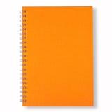 Cubierta anaranjada del cuaderno cercano Fotos de archivo