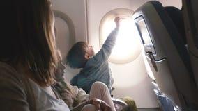 Cubierta curiosa feliz de la ventana del aeroplano de la abertura del niño pequeño durante el vuelo, disfrutando de la visión que almacen de video