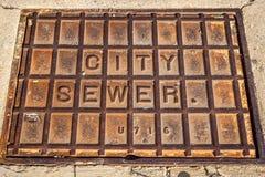 Cubierta de la alcantarilla de la ciudad en la calle imagenes de archivo