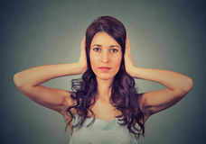 Cubierta de la mujer joven con las manos que sus oídos se cerraron No oiga ningún concepto malvado Foto de archivo