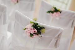 Cubierta de la silla de la boda con las flores rosadas Imagen de archivo libre de regalías