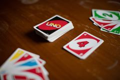 Cubierta de las tarjetas de juego del Uno dispersadas por todas partes en una tabla Juego de tarjeta americano foto de archivo