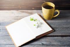 Cubierta de libro en blanco en el fondo de madera con la flor de la primavera y el cabo del café Imágenes de archivo libres de regalías
