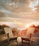 Cubierta de madera con las sillas, las dunas de arena y el océano Imagen de archivo libre de regalías
