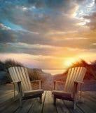 Cubierta de madera con las sillas, las dunas de arena y el océano Fotografía de archivo