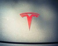 Cubierta de plata de la capilla del coche con el primer del logotipo de Tesla imágenes de archivo libres de regalías
