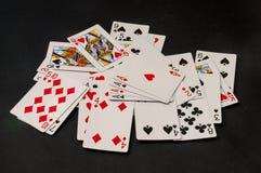 Cubierta de tarjetas dispersada en un fondo negro Fotografía de archivo libre de regalías